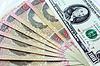 100-Dollar-Banknoten und grivnas auf dunklem Hintergrund | Stock Foto