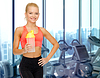 Happy woman with protein shake bottle in gym   Stock Foto