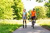 Glückliches Paar mit Rollschuhen und Fahrradfahren | Stock Photo
