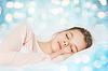 Niña durmiendo en la cama sobre fondo azul luces | Foto de stock