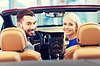 Happy couple sitting in car at auto show or salon | Stock Foto